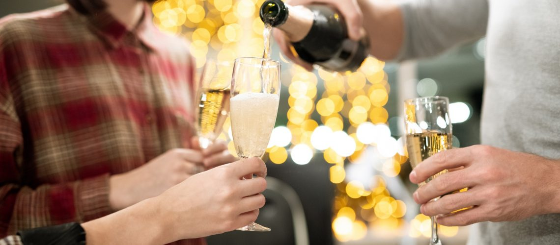hands-of-young-businesspeople-holding-flutes-while-going-to-have-champagne